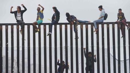 Migrant caravan demonstrators climb the US-Mexico border fence