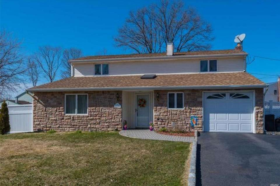 This Centereach Colonial includes four bedrooms and two