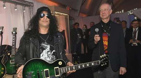 Recording artist Slash, left, is presented a one