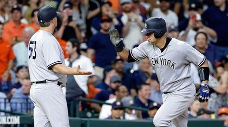 Yankees third base coach Phil Nevin congratulates Yankees