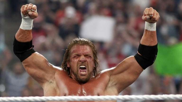 WWE Superstar Triple H celebrates his victory over
