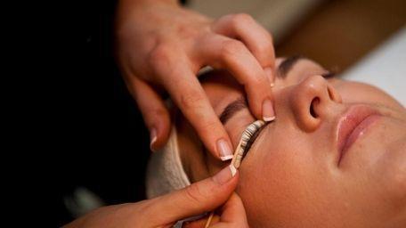 Taylor Roseberry applies eyelash dye to Kerri McCarthy