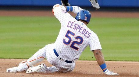 The Mets' Yoenis Cespedesslides under Braves second baseman