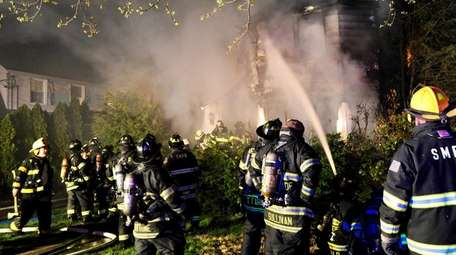 Firefighters work at a house fire on Argyle