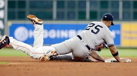 The Astros' Brian McCann is safe on the