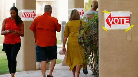 Voters arrive and depart a polling station.