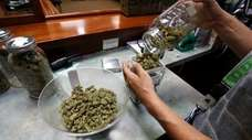An employee prepares marijuana for sale at The