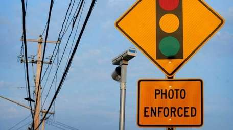 A sign and red-light camera are pictured on
