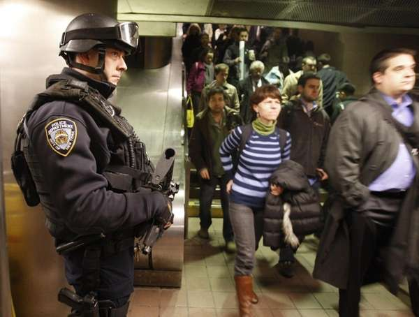 An NYPD counterterrorism officer watches commuters entering the
