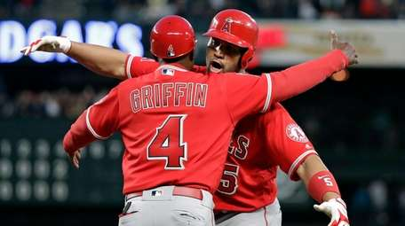The Angels' Albert Pujols, right, embraces first base