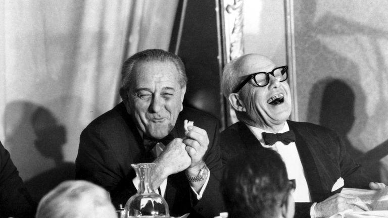 President Lyndon B. Johnson, munching on a cookie,