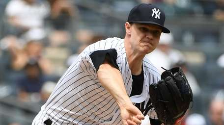Yankees starting pitcher Sonny Gray throws to first