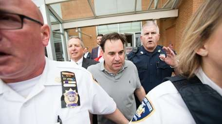 Suffolk County District Judge Robert Cicale is escorted