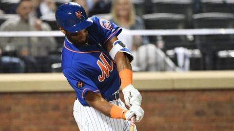 Mets shortstop Amed Rosario hits an RBI single