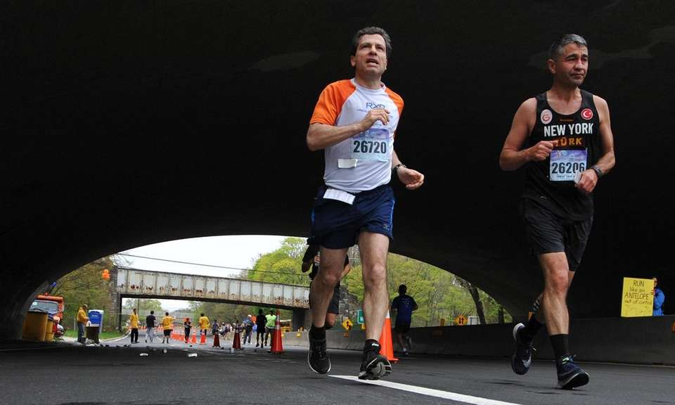 Marathoners run beneath the Sunrise Highway underpass on