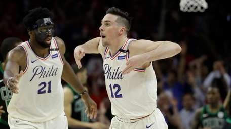 The 76ers' T.J. McConnell and Joel Embiid celebrate