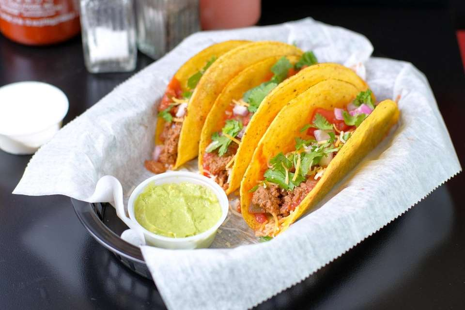 Beef tacos are topped with cilantro and salsa