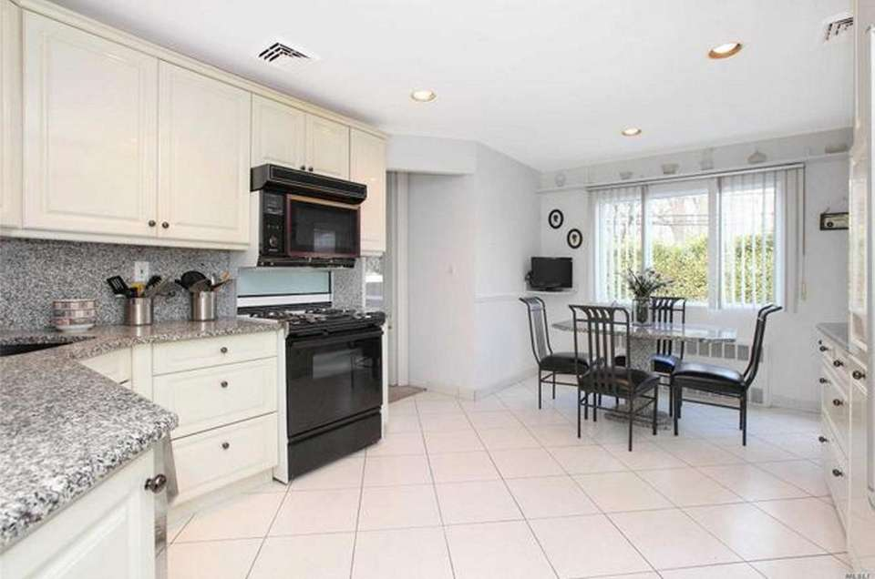 The kitchen in this Plainview split-level feature white