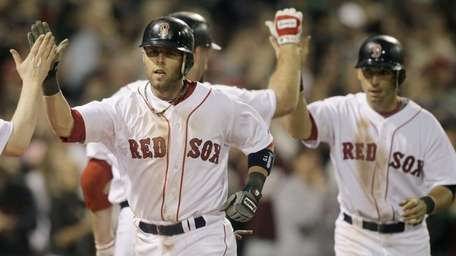 The Red Sox's Dustin Pedroia, left, is congratulated