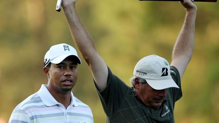 Tiger Woods, left, and Fred Couples walk across