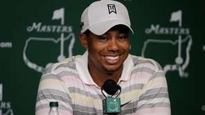 Tiger Woods smiles as he addresses members of