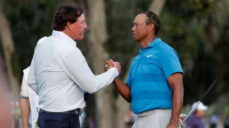 Phil Mickelson, left, and Tiger Woods shake hands