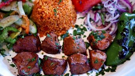 A lamb kebab platter is served with rice,