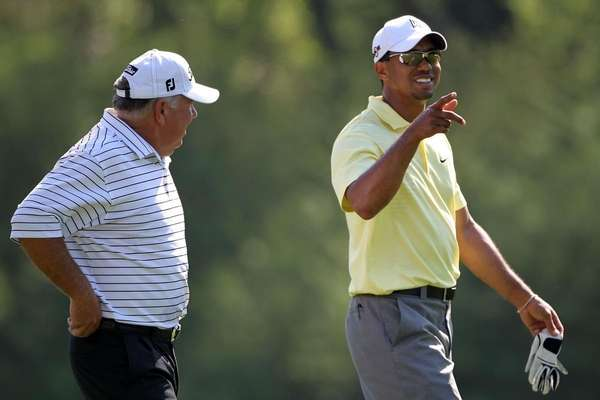 Tiger Woods (R) and Mark O'Meara walk together