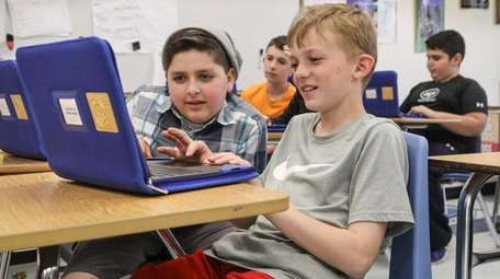 Sixth-graders Torre Cintorino, left, and Liam McGuire work