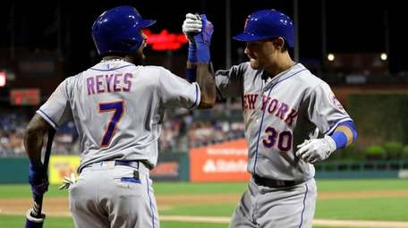 Mets outfielder Michael Conforto and Jose Reyes celebrate