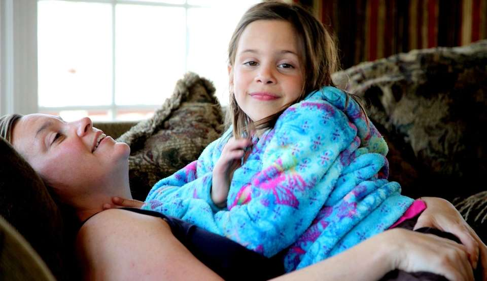 Katie Trebing, 7, sits with her mom at