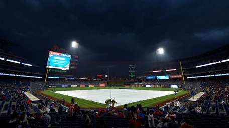 A tarp covers the field before a scheduled
