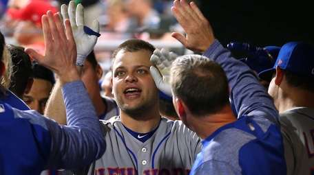 Devin Mesoraco is congratulated by teammates after