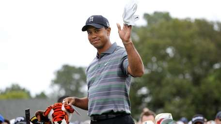 Tiger Woods waves to the gallery on the