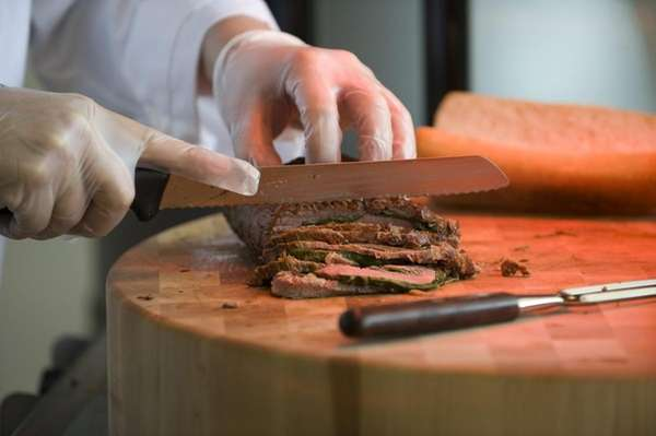 Sous-chef Camilo Baquero carves flank steak roulade, stuffed