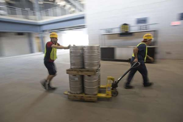 Workers take kegs of beer to the concession