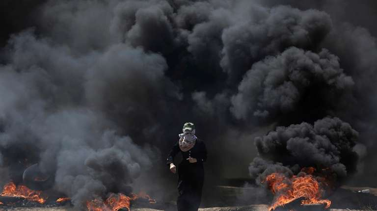 A Palestinian woman walks through black smoke from