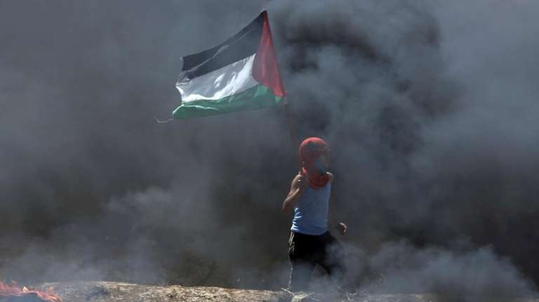 A boy waves a Palestinian flag while walking