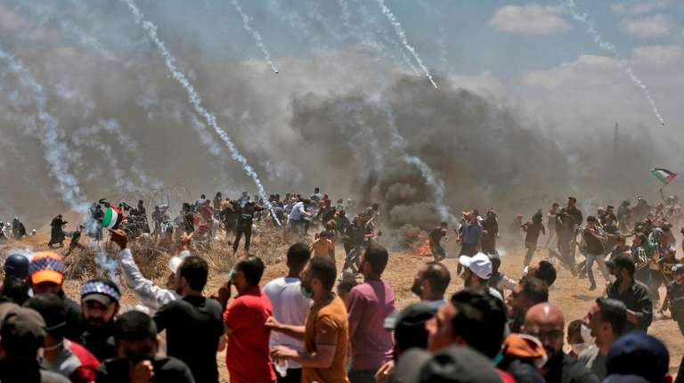 Palestinians run for cover from tear gas during