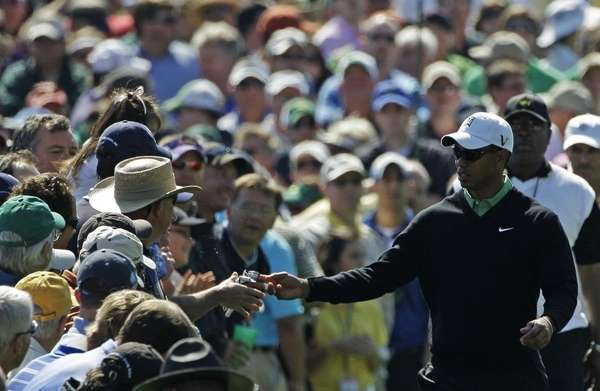 Tiger Woods gives his golfing gloves to a