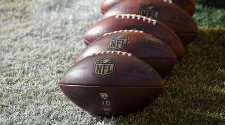 NFL footballs sit on the field during warm-ups