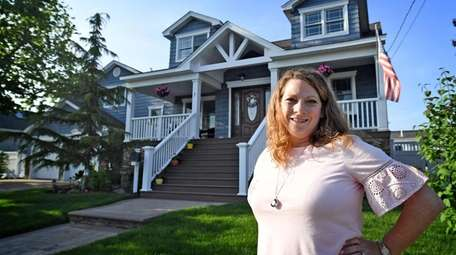 Kelly Harris in front of her three-bedroom waterfront