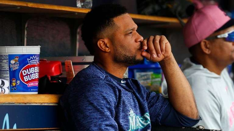 The Mariners' Robinson Cano sits on the bench