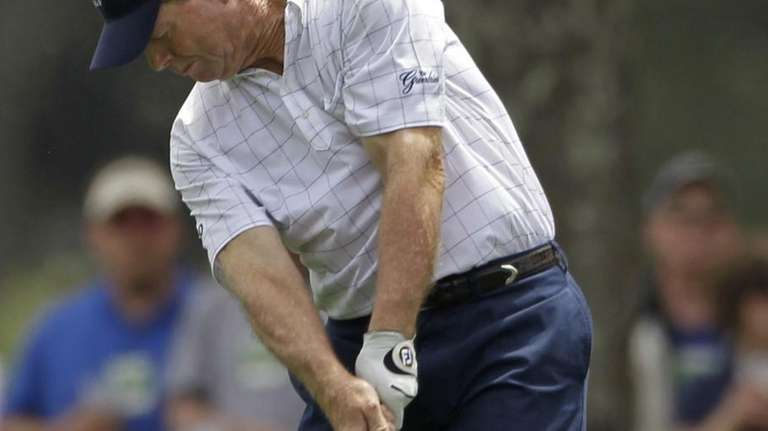 Tom Watson hits off the first fairway during