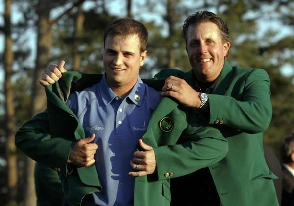 Zach Johnson, left, receives the Masters green jacket