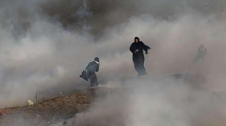 Two women struggle in a cloud of tear