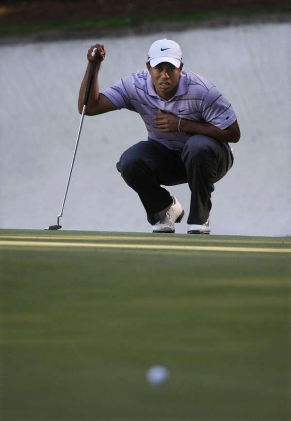 Tiger Woods looks over his birdie putt on