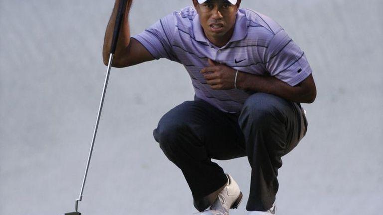 Tiger Woods looks over his birdie putt on