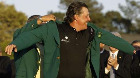 Phil Mickelson puts on the Masters jacket after