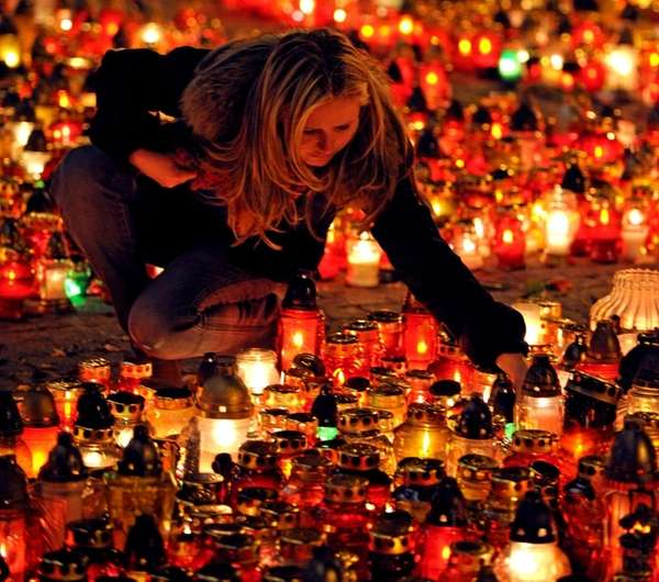 A woman lights candles placed by mourners in